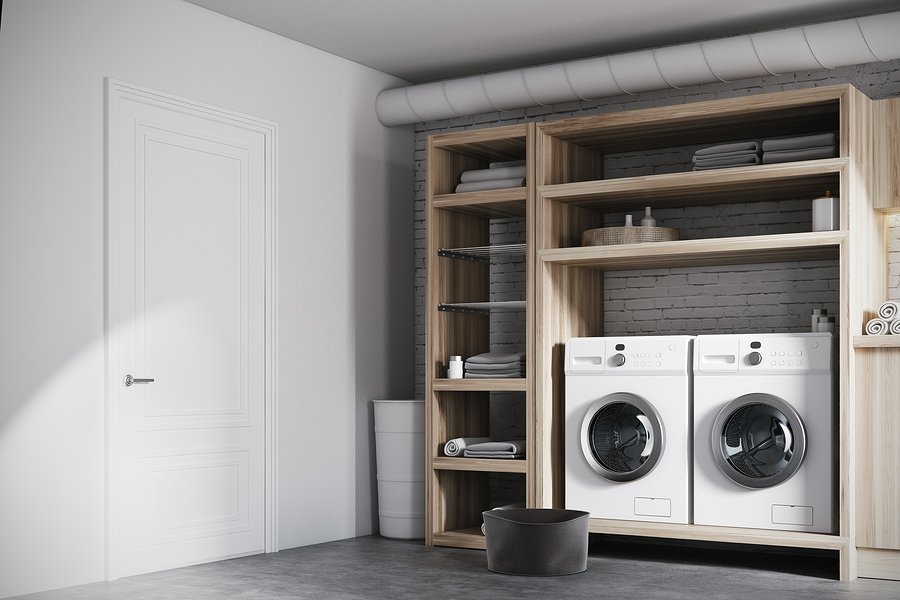 Modern laundry room interior with white brick walls wooden consoles and shelves with two white washing machines. Corner. 3d rendering