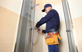 Plumber working in shower stall