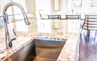 New modern faucet and kitchen room sink closeup with island and granite countertops in model house home apartment