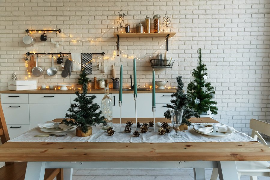 New Year and Christmas 2018. Festive kitchen in Christmas decorations. Candles, spruce branches, wooden stands, table laying.
