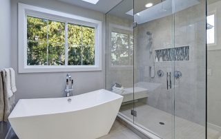 Glass walk-in shower with gray subway tiled surround and white freestanding tub in new luxury home bathroom. Northwest USA