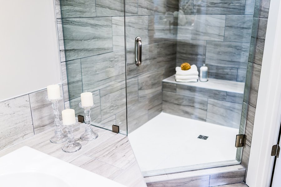 Closeup of staging modern stone grey tiled bathroom marble countertop in model home apartment or house with candles towels pouf soap dispenser glass shower door